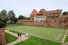 Historische Burgmauer der ehem. Ordensburg Thorn - Sportplatz und Hotelneubau.