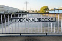 Inschrift Tidekanalbrücke; Lagerhäuser mit Krananlagen - Verwaltungsgebäude am Ufer vom Tidekanal in Hamburg Billbrook.