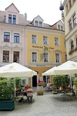 Aussengastronomie - Sitzplätze unter Sonnenschirmen auf dem Heinrichsplatz in Meißen - Restaurant, Hotel Goldener Löwe; erbaut im Stil des Historismus, zweite Hälfte des. 19. Jahrhunderts.