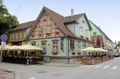 Landestypisches Holzhaus - Eckgebäude mit Fachwerkgiebel, Restaurant mit Terrassen am Strassenrand - Architektur in Pärnu, Estland.