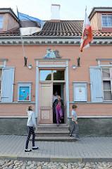 Eingang vom Spielzeugmuseum in Tartu - Flagge von Estland und Stadtfahne.
