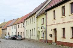 Straße / Fußweg mit Kopfsteinpflaster - geschlossene Wohnbebauung, einstöckige Wohnhäuser mit Satteldach; Fotos aus Schildau.