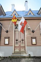 Holztür mit Schnitzerei - Flaggen am Hauseingang eines Holzgebäudes / Gasthauses in der Strasse Jaani in Tartu.