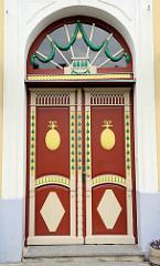 Holzdoppeltür, Eingang mit farblich abgesetzten Schnitzereien - Architekturform Historismus; Wohnhaus in Pärnu, Estonia.