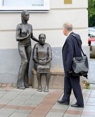 Bronzeskulpturen, Junge Frau - Alte Frau, Sitzbank vor dem Kunstimuuseum in Tartu - Mann mit Tasche betrachtet die Frauen.