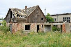 Altes verlassenes Ziegelgebäude mit Holzfassade, Giebelverkleidung - hohes Wildkraut / Unkraut an der Bahnhofstraße von Belgern.