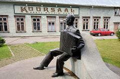 In Pärnu wurde 1838 das erste städtische Kurbad eröffnet; das historische Kurhaus / Kursaal wurde im Stil der Kurarchitektur 1893 errichtet. Bronzekulptur Akkordeonspieler; Fassadenschild Kuursaal.