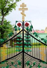 Schmiedeeisernes Tor der Christi Verklärungskirche der Orthodoxen Kirche von Estland in Pärnu; Jugendstilranken mit roten Blüten, goldenes russisches Kreuz - Orthodoxes Kreuz, Byzantinisches Kreuz