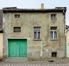 Wohnhaus mit Tor in der Pfarrstraße von Belgern; abgebröckelter Putz - Reste von  Fassadendekor.
