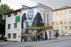 Fassadenmalerei - Bild auf einer Hausfassade in Tartu; Frau mit Strick + schwarzen Flügeln: Mrs REET / Streetartist - französicher Graffiti-Künstler MTO - Stencibility festival in April 2014.