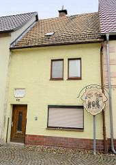 Schmales Wohnhaus aus dem 17. Jahrhundert in Schildau - Schild der Geschichte der Schildbürger mit dem Maushund.