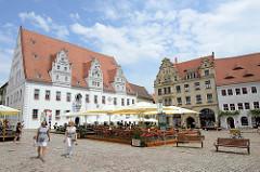 Historische Altstadt von Meißen - Marktplatz, Aussengastronomie unter Sonnenschirmen; Blick auf das Rathaus der Stadt - fertiggestellt 1486, Baustil der Spätgotik. Rechts das sogen. Hirschhaus, erbaut 1901.
