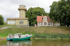 Leuchtturm, Leuchtfeuer am Fluss Pärnu; Holzhaus des Leuchtturmwärters, Ausflugsboot am Ufer.