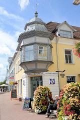 Sitzbank zwischen prunkvoll blühenden Blumentöpfen - Eckgebäude mit Erkerturm über dem Hauseingang; Nikolai / Pärnu.