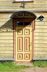 Eingangstür / Holztür mit farblich abgesetztem Türrahmen, Leisten - halbrundes Regendach mit Schmiedeeisen; Straße Marja in Tartu.