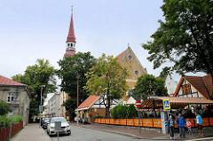 Blick in die Straße Nikolai - Restaurant mit Aussengastronomie - Kirchturm / Kirchenschiff der Elisabeth-Kirche in Pärnu; geweiht 1750.
