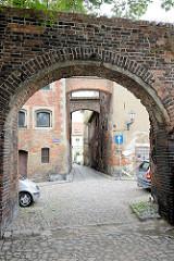 Schmale Gasse mit Ziegelmauer und gemauerten Hausstützen, Kopfsteinpflaster in Toruń.