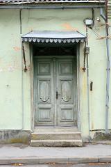 Alte Haustür, Holztür mit Dekorfüllung und verziertem Blechdach / Regenschutz; Architekturbilder aus Pärnu, Estland.