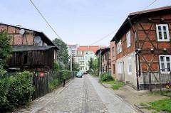 Wohnstraße mit Kopfsteinpflaster in Toruń; historische Bebauung mit Fachwerkgebäuden.