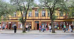 Geschäftshäuser mit Holzfassade - Fassade farbig abgesetzt; Menschen an der Bushaltestelle - Rüütli in Pärnu, Estland.