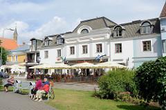Grünanlage an der Munga in Pärnu - Sitzbänke in der Sonne; Café mit Terrasse unter Sonnenschirmen.