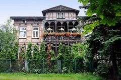 Fachwerkvilla mit Holzbalkon und Ziergiebel - blühende Geranien; Architektur in Toruń.