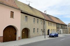 Wohnhäuser mit halbrunden Toreinfahrten, geschlossene Wohnbebauung - Straße in Schildau.