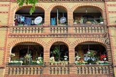 Balkons eines Wohnhauses in Toruń - gelbe Ziegelfassade mit roten Ziegelbändern - Blumenkästen und Wäsche.