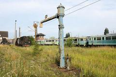 Preussischer Wasserkran zum Füllen von Dampflokomotiven - im Hintergrund stillgelegt Personenzügen und Dampfloks.