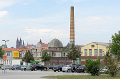 Panorama von Meißen - Supermarktparkplatz, Gewerbe und Kultur, im Vordergrund Fabrikschornstein und Fabrik der Keramischen Fabrik Bidtelia, errichtet 1881 - im Hintergrund die neogotischen Kirchtürme vom Dom auf dem Burgberg.