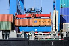 Verladung von Containern im Hamburger Hafen - zwei Standardcontainer / TEU hängen an der  Containerbrücke über dem Frachter.