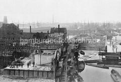 Abriss von Gebäuden auf dem Kehrwieder - Vorbereitung zum Bau der Hamburger Speicherstadt - im Hintergrund  Segelschiffe im Niederhafen; lks. der Uhrenturm vom Kaiserspeicher.