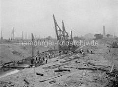 Bau vom Baakenhafen in dem jetzigen Hamburger Stadtteil Hafencity - Bauarbeiter / Baumaschinen heben das Hafenbecken aus; lks. Masten von Schiffen in der Norderelbe, im Hintergrund die Gasanstalt auf dem Grasbrook.