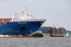 Cargo Ship GOTLAND in voller Fahrt auf der Elbe; der Wulstbug den Wasserwiderstand. Im Hintergrund ein historischer Kutter / Ewer mit braunen Segeln und ein Sportsegelboot.