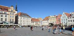 Historische Häuser am  Rathausplatz / Raekoja plats von Tallinn - Restaurants und Cafés in der Sonne, Touristen schlendern über den Marktplatz.