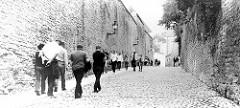 Alte Straße mit Kopfsteinpflaster an der Burgmauer in Tallinn;  Pikk jalg / Langer Domberg - Fußgänger, Touristen.