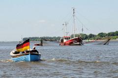 Ein Tuckerboot / Holzboot fährt mit großer Deutschlandfahne elbaufwärts - der Fischkutter HBK 103 hat seine Netze ausgelegt. Der Kutter Luise wurde 1950 gebaut und hat eine Länge von 16 m.