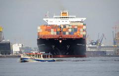 Der 335m lange Containerriese FRANKFURT EXPRESS läuft aus dem Hamburger Hafen aus. Das Frachtschiff hat eine Tragfähigkeit von 84300 t und kann 8749 TEU Container laden. Die Barkasse des Oberhafenamts kreuzt das Fahrwasser des Riesenschiffs.