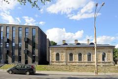 Alt + Neu; moderne Wohngebäude mit Ziegelfassade und Schrägdach neben einem historischen Haus mit gelber Klinkerfassade, Zierbändern und Feldsteinfundement; Straße Mickevičiaus  in Vilnius.