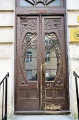 Historische Jugendstiltür / Art Nouveau in Vilnius; geschwungene Fenster in der Doppeltür, Leisten und Schnitzwerk als florales Rankwerk.