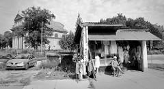 Straßenverkauf von Kleidung bei den Bahngleisen in Olsztyn - Hütte mit Wellblechdach, die Verkäuferin sitzt vor ihrem Laden in der Sonne. Im Hintergrund die Christ König und Franz von Assisi Kirche,  erbaut 1927 - neoklassizistischer Baust