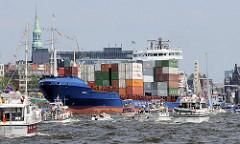 Das Cargo Vessel HERM J fährt Höhe St. Pauli Landungsbrücken auf der Elbe im Hamburger Hafen.Die Containerladung ist hoch an Deck des Feeder Schiffs gestapelt. Eine größere Anzahl von Motorboote fahren auf dem Hamburger Fluss elbaufwärts.