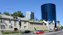 Traditionelle Holzarchitektur - einstöckige Wohnhäuser in Holzbauweise - großer schwarzer runder Büroturm mit Glasfassade; Bankgebäude an der Straße Liivalaia in Tallinn.