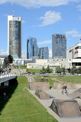 Fussgängerbrücke Baltasis tiltas / Weiße Brücke über die Neris; Panorama der modernen Hochhäuser im Stadtteil Šnipiškės in Vilnius. Re. der Sportpark am Ufer der Neris - Sprungschanze und Halfpipe für bikes.