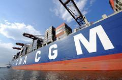 Weisser Schriftzug der französischen Reederei CMA CGM an der Schiffswand des Containerriesen CHRISTOPHE COLOMB, der unter den Containerbrücken des Hamburger Terminals Bruchardkai.