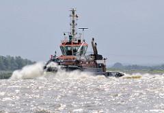 Bild des Hamburger Schleppers BUGSIER 5 in voller Fahrt auf der Elbe; die Gischt spritzt am Bug des Arbeitsschiffs hoch auf. Die Maschine des 2008 gebaute Hafenschlepper hat eine Leistung von 4 800 kW / 6530 PS. Das Hamburger Arbeitsschiff hat eine
