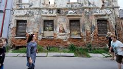 Alte Hausfassade, Hausruine mit vernagelten Fenstern und Graffiti / Stencil in Kaunas.