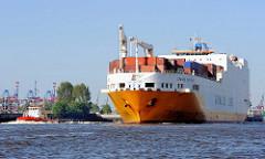 Das RoRo Schiff GRANDE SAN PAOLO läuft in den Hamburger Hafen ein. Ein Hafenschlepper unterstützt das Frachtschiff bei seiner Fahrt zu seinem Liegeplatz.