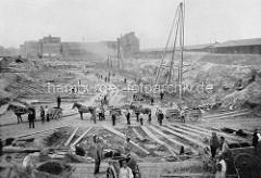 Baustelle auf dem Areal der zukünftigen Hamburger Speicherstadt - Bauarbeiter mit Pferdewagen und Handkarren transportieren den Aushub - im Hintergrund alte Wohnhäuser, re. Lagerschuppen am Sandtorhafen.