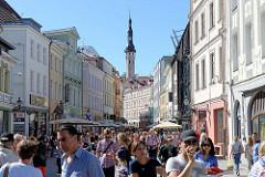 Fussgängerzone - Geschäftsstraße Viru in Tallinn - Fußgänger*Innen und Touristen in der Sonne. Im Hintergrund der spätgotische Turm vom Tallinner Rathaus.